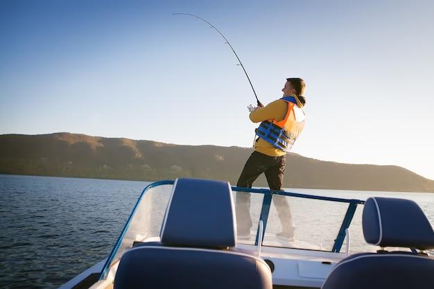 Giovane che pesca da una barca