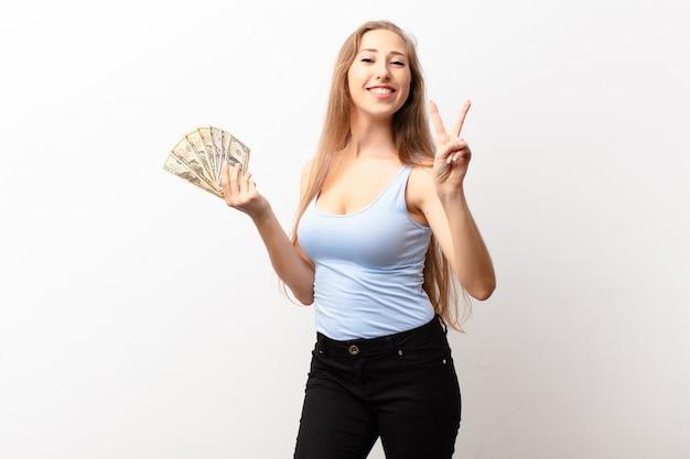 Yound donna bionda sorridente e guardando felice, spensierata e positiva, gesticolando vittoria o pace con una mano che tiene le banconote in dollari