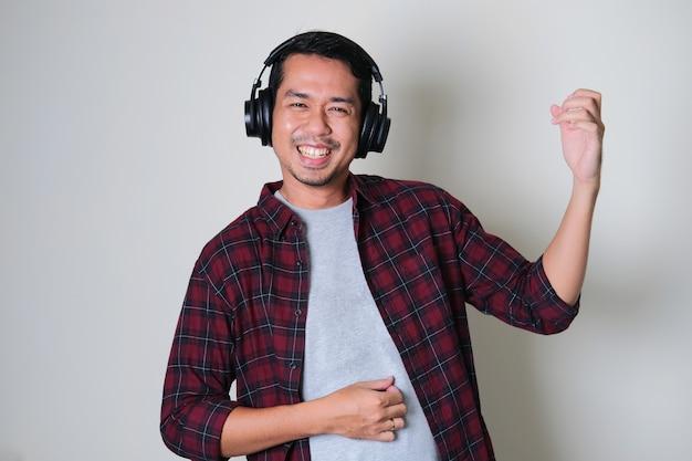 Giovani uomini asiatici attivi che sorridono felici mentre indossano le cuffie e si mettono in posa come suonare la chitarra