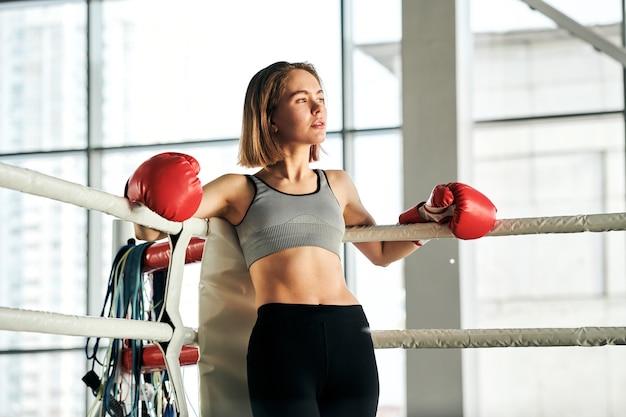 Giovane donna bionda attiva in guantoni da boxe rossi e tuta appoggiata contro le barre pur avendo riposo dopo l'allenamento in palestra