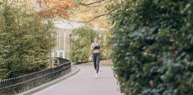 Giovane esercitazione femminile attiva dell'atleta all'aperto in autunno soleggiato
