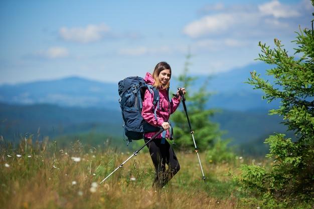 Giovane scalatore femmina attivo con zaino e bastoncini da trekking, trekking in montagna, godendo la giornata di sole. concetto di stile di vita attivo