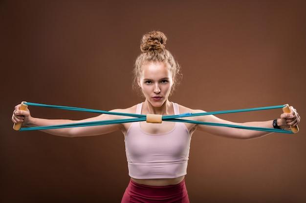 Giovane donna attiva in tuta che allunga la fascia elastica davanti a se stessa