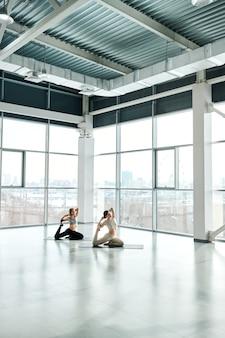 Giovani femmine attive in abiti sportivi che praticano esercizi yoga su stuoie durante l'allenamento nella grande palestra o nel centro ricreativo