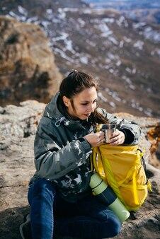 Una giovane ragazza attiva beve tè caldo, tiene in mano uno zaino giallo, siede sul bordo di una scogliera