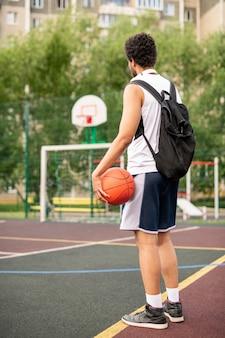 Giovane giocatore di basket maschile attivo con palla e zaino in piedi dalla linea bianca sul campo da giuoco