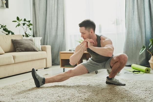 Giovane uomo attivo in abiti sportivi facendo esercizio di stretching per le gambe sul tappeto in soggiorno mentre trascorre le giornate a casa