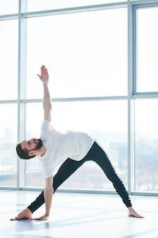 Giovane uomo attivo con le gambe tese flessione laterale con il braccio sinistro sollevato mentre si allena in palestra