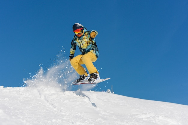 Giovane snowboarder attivo in abiti sportivi luminosi che salta su un pendio di montagna