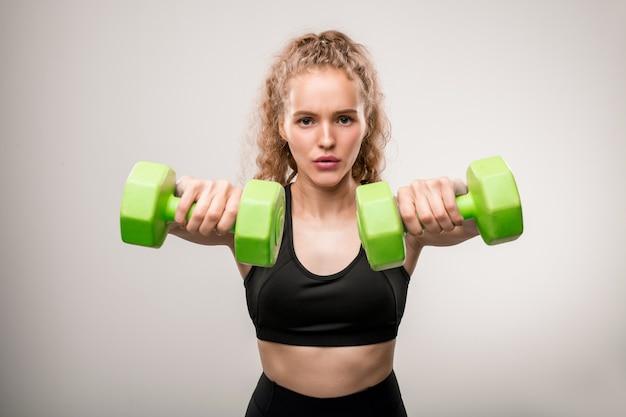 Giovane sportiva attiva in tuta nera e facendo esercizio con manubri verdi