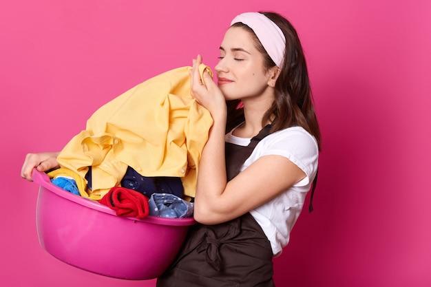 Giovane casalinga sorridente adorabile che cammina con il bacino rosa in una mano