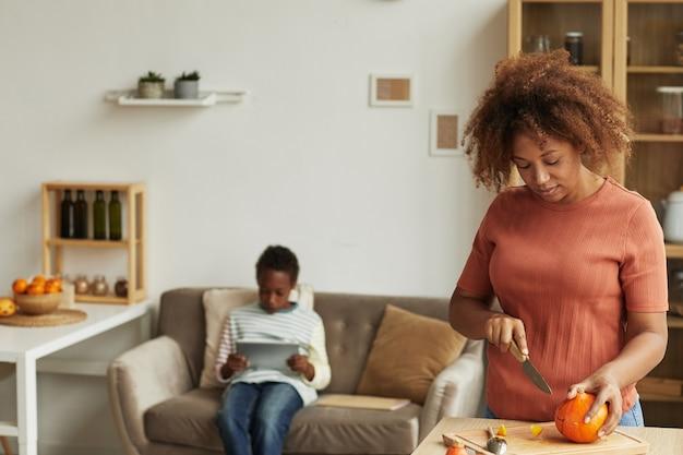 Giovane donna afroamericana adulta che intaglia la zucca per la festa di halloween mentre suo figlio si siede sul divano e guarda qualcosa sulla tavoletta digitale