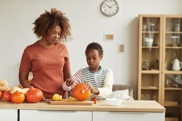 Giovane donna afroamericana adulta che indossa abbigliamento casual in piedi al tavolo a guardare il suo bambino intagliare la zucca