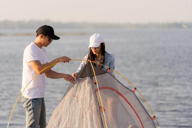 La giovane coppia asiatica adulta lancia e installa la tenda per il campeggio intorno al lago.