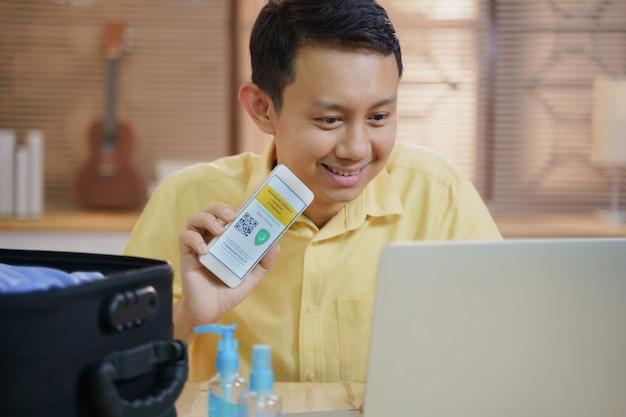 Il giovane maschio asiatico adulto si siede in soggiorno felice ed entusiasta di ottenere il documento di viaggio del passaporto del vaccino contro il coronavirus covid-19 certificato dall'app del telefono cellulare mentre si utilizza il laptop e si è pronti a viaggiare
