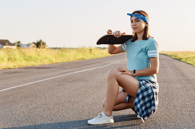 Giovane ragazza attraente adulta con i capelli scuri in posa con un longboard sulle spalle mentre è seduta per strada in estate, guardando lontano con espressione pensosa.