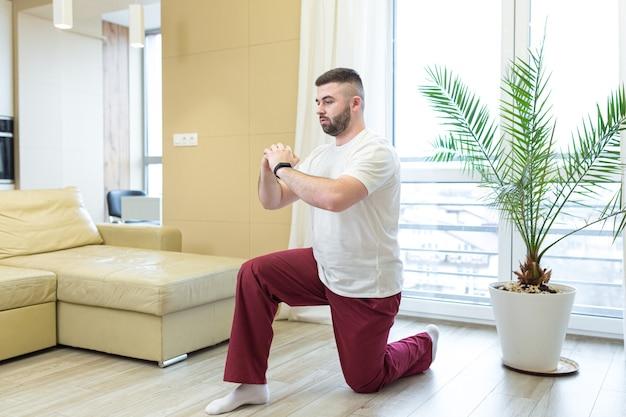 Giovane uomo barbuto adulto che fa esercizi di stretching a casa in soggiorno guardando lezione video o tutorial online usando un laptop uomo che fa fitness e sport al mattino seduto sul pavimento