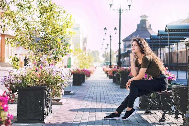 Giovane bella ragazza castana adulta in abiti casual felice sulla strada della città