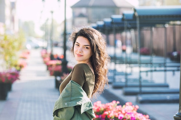 Giovane bella ragazza castana adulta in vestiti casuali che cammina felice intorno alla città