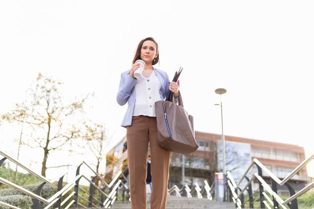 Giovane bella donna d'affari adulta che beve caffè per strada lasciando il lavoro con il caffè per andare a laptop e cartella. concetto di donna d'affari di successo