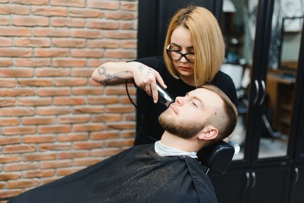 Il parrucchiere giovane adulto bella donna caucasica taglia la barba bell'uomo al moderno barbiere felice gay seduta sedia uomini salone di bellezza.