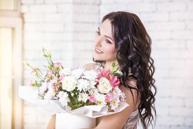 Giovane bella donna adulta in un vestito festivo alla moda lungo con un mazzo di fiori