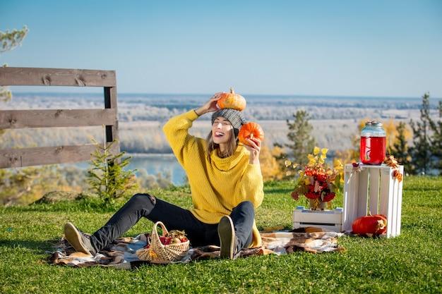 Giovane bella donna adulta in natura durante un picnic con plaid, zucche e paesaggi autunnali