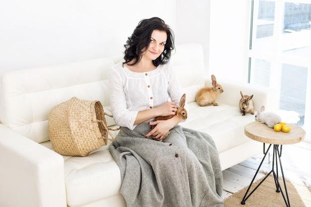 Giovane bella donna adulta con soffici conigli e uova di pasqua seduta su un divano bianco