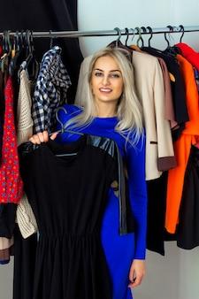 Giovane donna bionda adulta sorridente e scegliendo un vestito nel negozio di abbigliamento