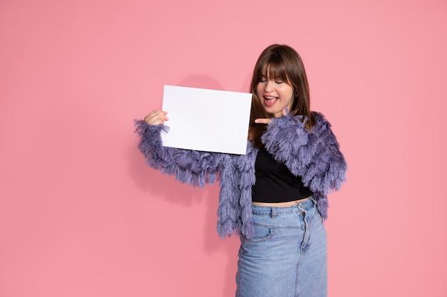 Giovane adulto dai capelli castani donna in piedi e mostrando con il dito su sfondo rosa con lavagna vuota per il segno su sfondo rosa in studio. sorpreso, eccitato. ritratto