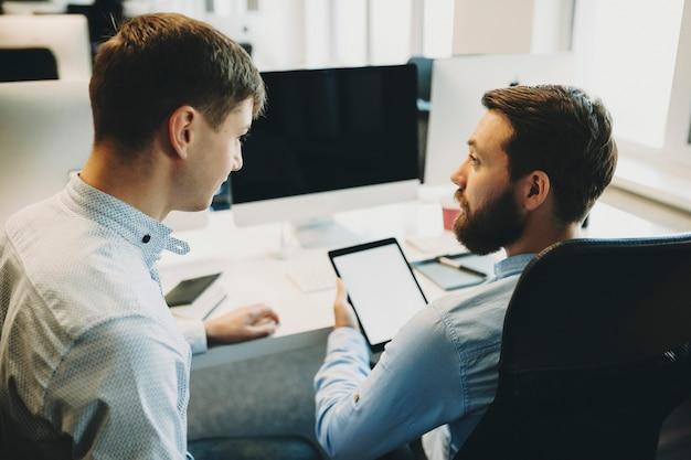 Giovani e adulti che collaborano uomini che lavorano con tavoletta digitale alla scrivania in ufficio