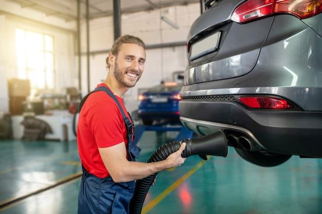 Giovane adulto fiducioso uomo in uniforme da lavoro lavorando su automobili