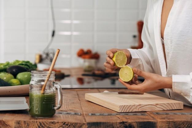 Giovane adulto che taglia la calce aperta. preparare la colazione con succo verde sul bancone della cucina. cannuccia di bambù riutilizzabile. concetto di stile di vita sano. concetto di casa. copia spazio.