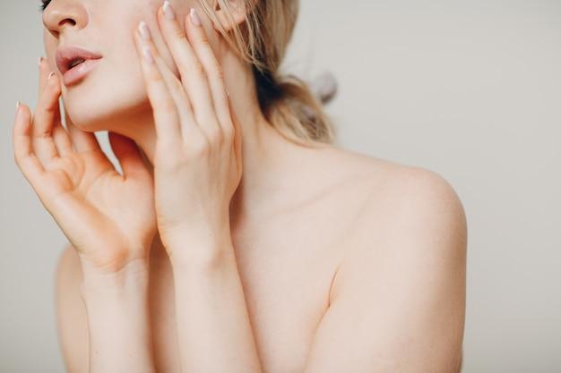 Giovane adulto che fa ginnastica facciale automassaggio ed esercizi di ringiovanimento del viso per il sollevamento della pelle e dei muscoli