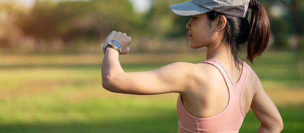 Giovane femmina adulta che controlla il tempo e la frequenza cardiaca cardio su smartwatch sportivo durante la corsa nel parco all'aperto, donna corridore fare jogging al mattino. esercizio, tecnologia, stile di vita e allenamento