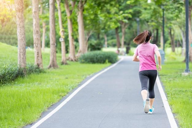 Giovane femmina adulta in abiti sportivi in esecuzione nel parco all'aperto