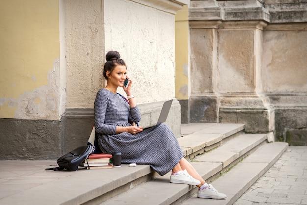 Giovane studentessa adulta parlando di smartphone seduto sulle scale con il computer portatile vicino al palazzo dell'università