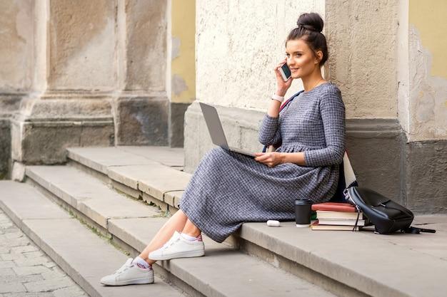 Giovane studentessa adulta che parla dallo smartphone che si siede sulle scale con il computer portatile vicino al palazzo dell'università