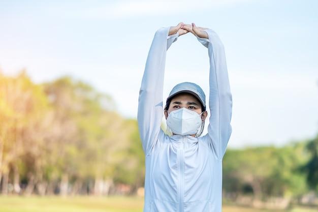 Giovane femmina adulta che indossa la maschera protettiva n95 durante lo stretching muscolare nel parco all'aperto