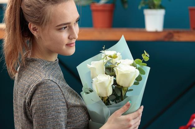 Una giovane fioraia adulta tiene un mazzo di rose e guarda al lato.