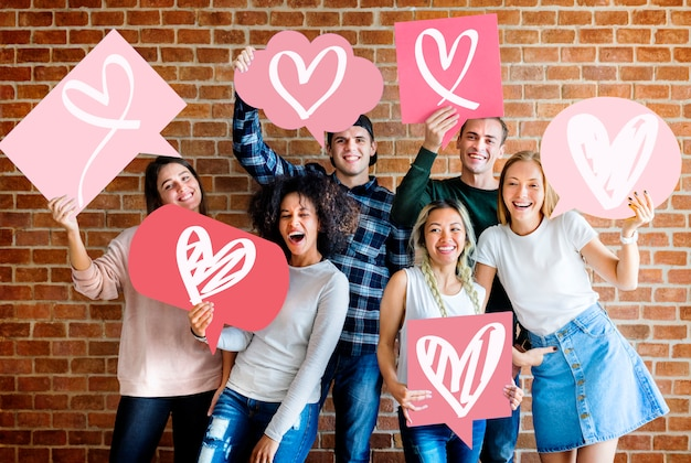 Giovani amici adulti che tengono le icone del cuore