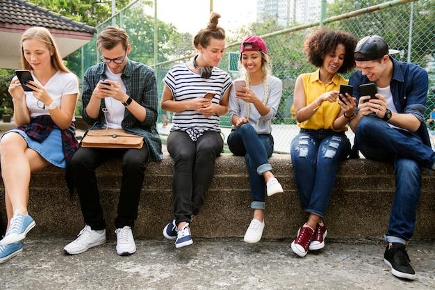 Giovani amici adulti che utilizzano insieme gli smartphone concetto di cultura della gioventù all'aperto