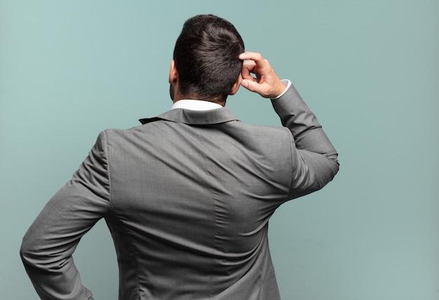 Giovane uomo d'affari bello adulto che si sente incapace e confuso, pensando a una soluzione, con la mano sull'anca e l'altra sulla testa, vista posteriore