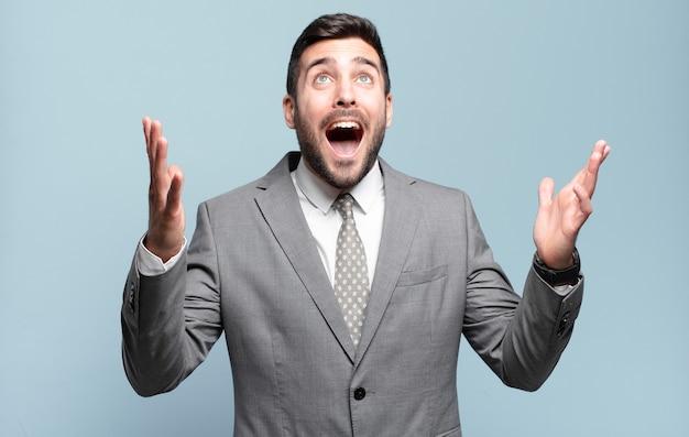 Giovane uomo d'affari bello adulto che si sente felice, stupito, fortunato e sorpreso, celebrando la vittoria con entrambe le mani in aria