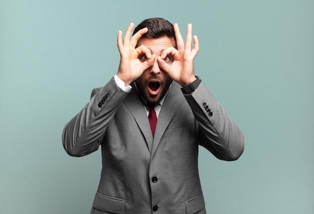 Giovane uomo d'affari adulto bello sentirsi scioccato, stupito e sorpreso, tenendo gli occhiali con uno sguardo stupito e incredulo