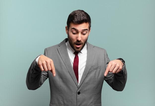 Giovane uomo d'affari bello adulto sentirsi scioccato, a bocca aperta e stupito, guardando e puntando verso il basso con incredulità e sorpresa