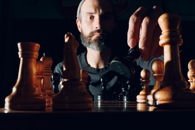 Giovane adulto bello che gioca a scacchi al buio con il lato illuminato