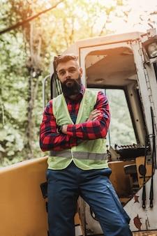 Giovane boscaiolo adulto o logger in piedi di fronte a un enorme escavatore bagger nel bosco