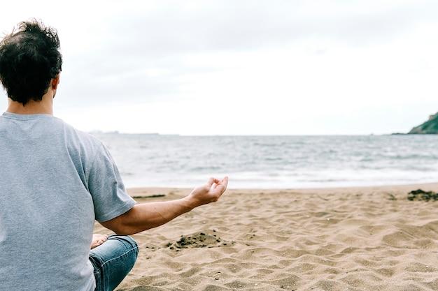 Giovane uomo adulto sulla spiaggia seduto in posizione yoga meditando