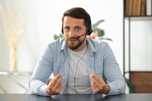 Lavoratore o manager del call center di giovane uomo adulto in cuffia guardando la webcam, avendo riunioni di lavoro online. ritratto di un dipendente di successo che comunica con i colleghi tramite videochiamata